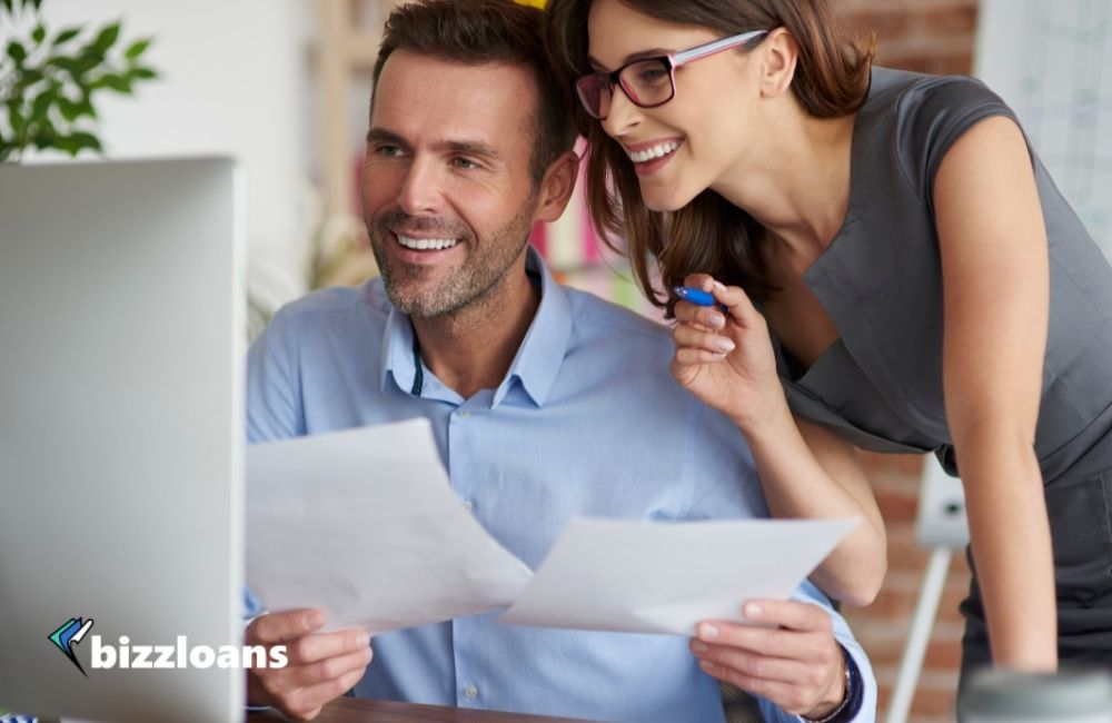 business owners happily looking at their approved business loan in the desktop